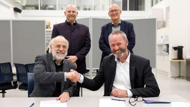 Foran fv: HSN-rektor Petter Aasen og konserndirektør i Kongsberg Gruppen Hans Petter Blokkum signerer kontrakten mellom høyskolen og Kongsberg Defence & Aerospace (KDA). Foto