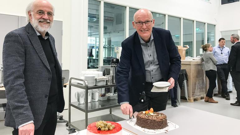 Tradisjonen tro ble ansettelsen av ny FoUI-ekspert markert med kake. Fv: Rektor Petter Aasen og Roar Uttisrud, som fikk ta det første stykket. Foto: Jan-Henrik Kulberg