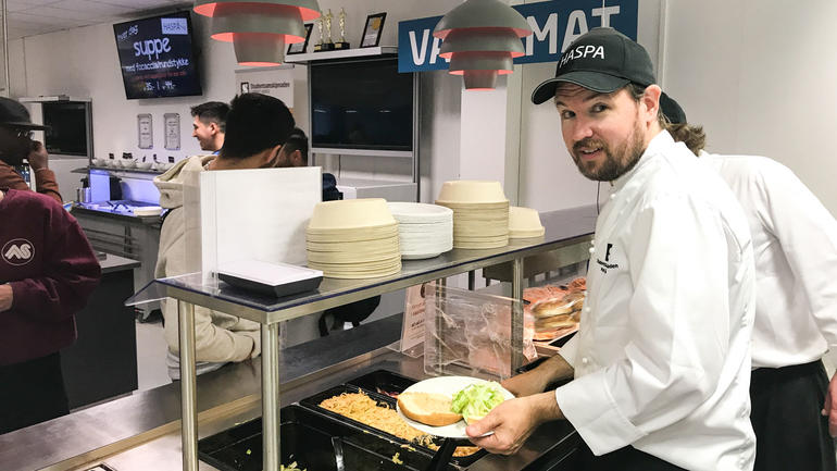 Simon Hogstad serverer hamburger til studenter og ansatte på campus Kongsberg. Foto