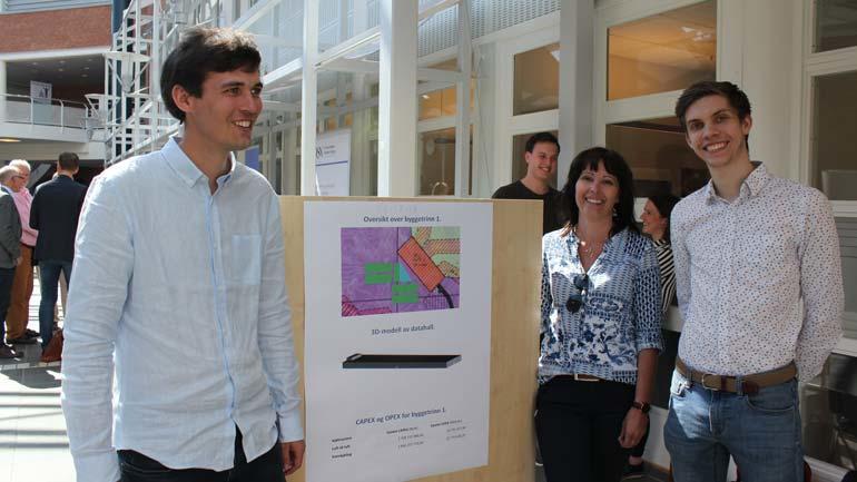 Elkraftstudentene Wilhelm, Eldrid og Håvard viser frem sitt prosjekt på postere i Glassgata.