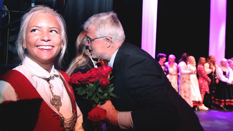 Lærerstudent smiler bredt på scenen når får utdelt roser.