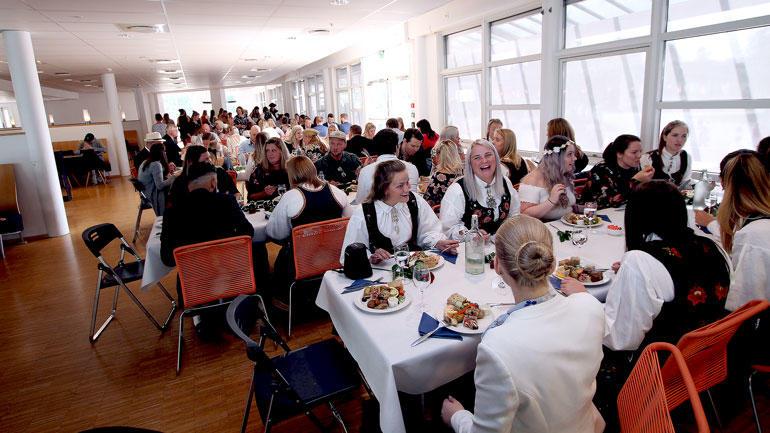 Nyutdannede lærere som spiser ved bordene som er dekket med hvite duker i studentkantina ved campus Vestfold.