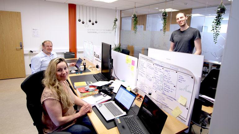 Miljøet i studentinkubatoren og tre studenter som bruker kontorlandskapet ved USN campus Vestfold