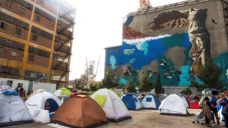 Flyktninger fra krigen i Syria blant bygninger og veggmalerier ved havnen i  Pireus ved Athen. Foto: iStock/AshleyWiley