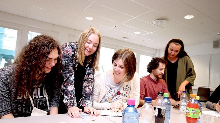 USN-studentene som er med å utvikle appen står rundt bordet og hjelper de unge italienerne som er prøvekaniner.