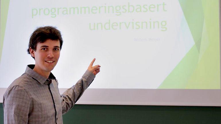 Ingeniørstudent Willem Meijer foran lerretet  med presentasjonen sin om programmeringsbasert undervisning.