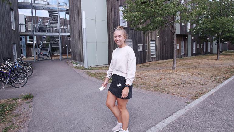 Fersk student Camilla Tomta med nøkkelkortet i hånda spaserer utenfor studentbygget ved USN campus Vestfold.