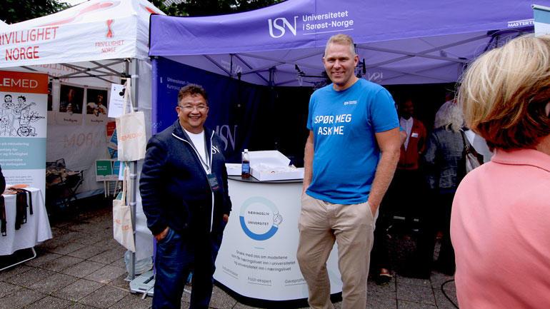 prosjektleder for USN Partnerskap, Duy Tho Do og seniorrådgiver Lars Gunnar Sønsteby på standen til USN på Arendalsuka