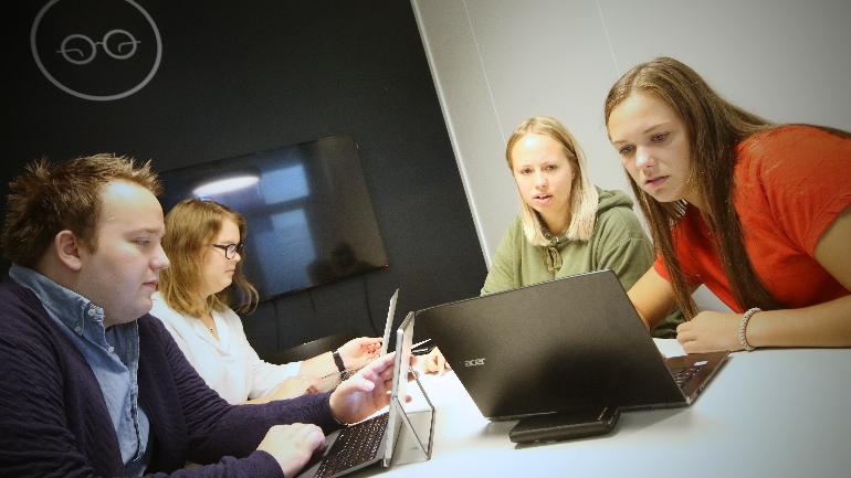 Andreas Ek Pedersen, Mari Telise Nilsen, Ida Groven og Linn Cecilie Solberg sitter inne på et av campus Drammens grupperom og diskuterer innholdet i den digitale kunnskapsreisen. foto.