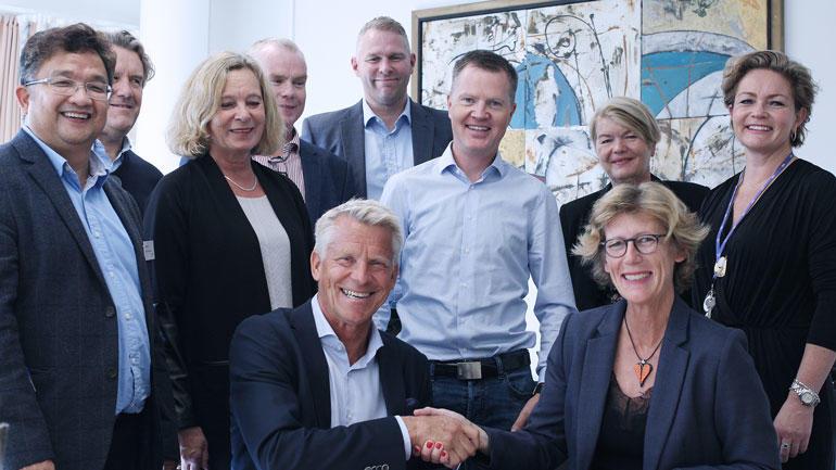 Gruppebilde av signeringen. Prorektor Nils Kristian Bogen og daglig leder Hanne Gro Haugland i Vekst i Grenland shaker hands.