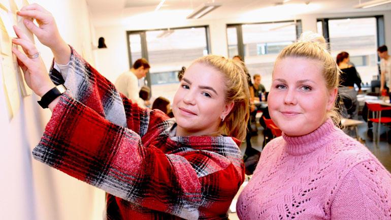 To studenter henger opp gule lapper på Profesjonsverksted
