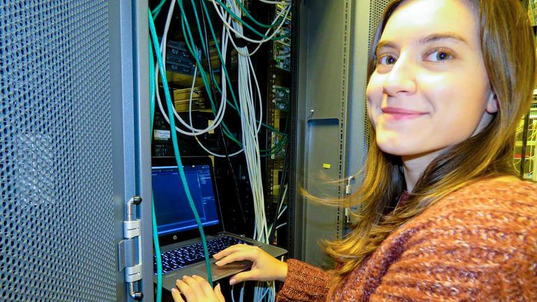 Eleonora Ntreska jobber som IKT Integrasjonsrådgiver, og er dataingeniør fra USN. Foto av henne ved dataskap. Bli dataingeniør du også.