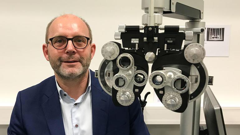 Martin Rostrup fra Rodenstock Norge blir USNs nye ekspert innen FoUI (forskning, utvikling og innovasjon). Fotografert med et av apparatene som firmaet har levert til USN. Bli optiker på USN.