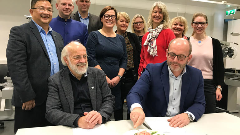 Rektor Petter Aasen spanderte kake på Martin Rostrup i anledning signeringen. USN-ansatte i bakgrunnen. Foto