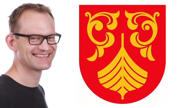 Bjørn Bandlien ved siden av forslaget til våpenskjold for Vestofld og Telemark fylkeskommune. Fotomontasje