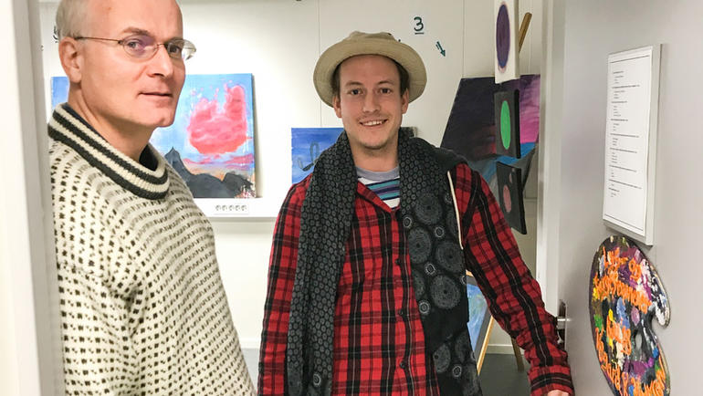 Velkommen inn: F.v. Universitetslektor Jan Henrik Wold og student Vegard Kvennejorde Knutsen i døråpningen til utstillingslokalet på campus Kongsberg.  Foto av de to i døråpning. Bli lysdesigner på USN.