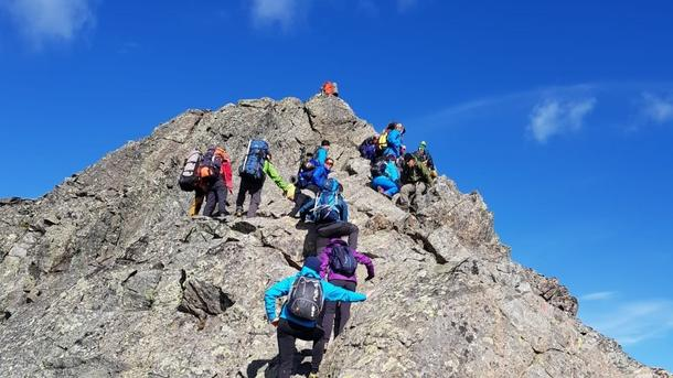 students climbing up a mountain