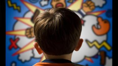 Illustrasjonsbilde med bakhode til et barn som ser en tegneserievegg med vold