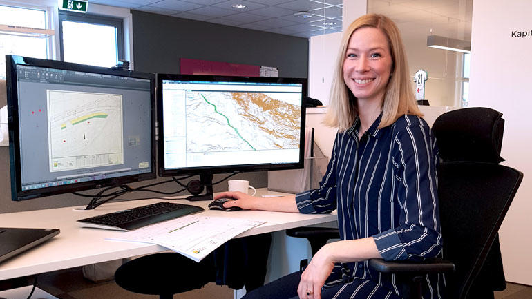 Ann Gøril Nykås ved arbeidspulten sin og to dataskjermer i bakgrunnen