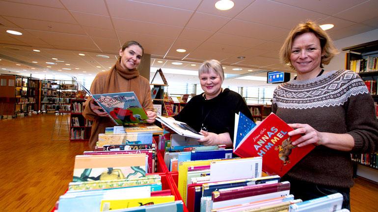 Tre fra USNs festivalledelse viser frem bildebøker på biblioteket.
