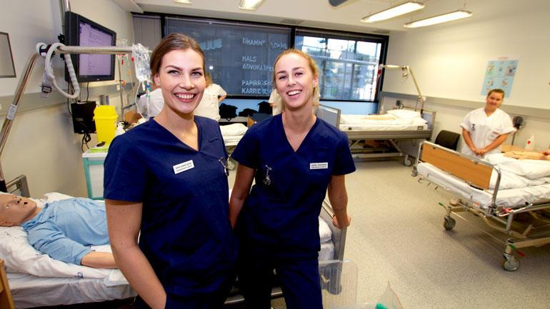 SykepleierstudenteneSunniva Landsverk og Synne Poortman i et simuleringsrom med sykehussenger ved campus Drammen.