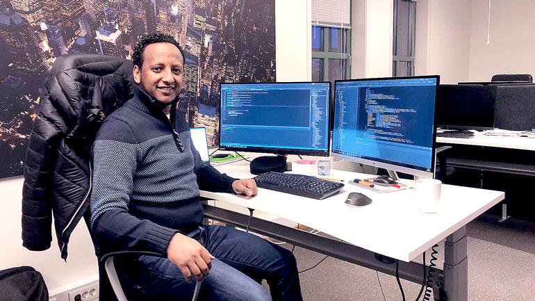Amanuel K. Tedla sittende foran to datamaskiner