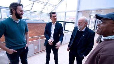 Konsernsjef Geir Håøy fra Kongsberg Gruppen og USN-rektor Petter Aasen i dress i samtale med to USN-studenter på campus Porsgrunn
