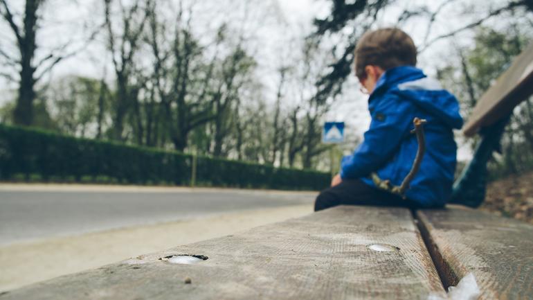 Gutt som sitter ensom på fortauet