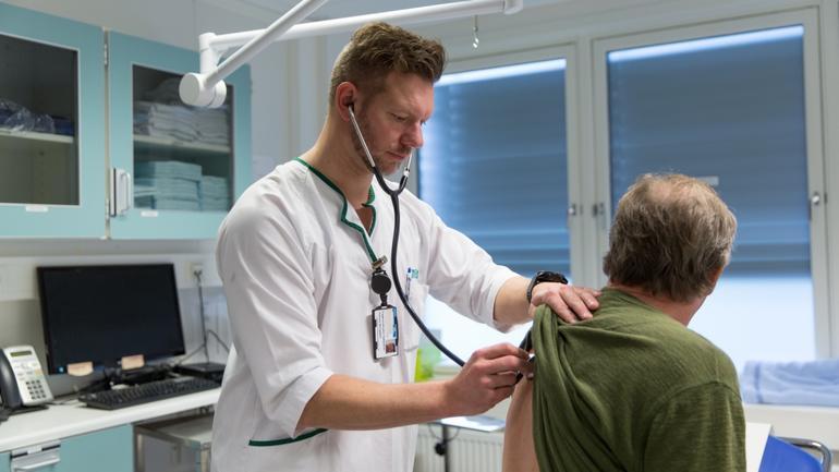 En avansert klinisk sykepleier som undersøker en pasient.
