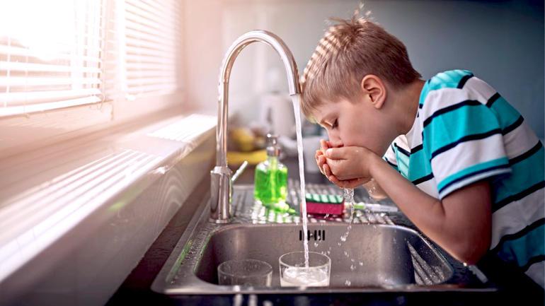 Gutt som drikker vann fra spingen på kjøkkenet