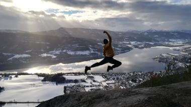 Exchange student Mihailo jumping in front of a view of the river in Kongsberg