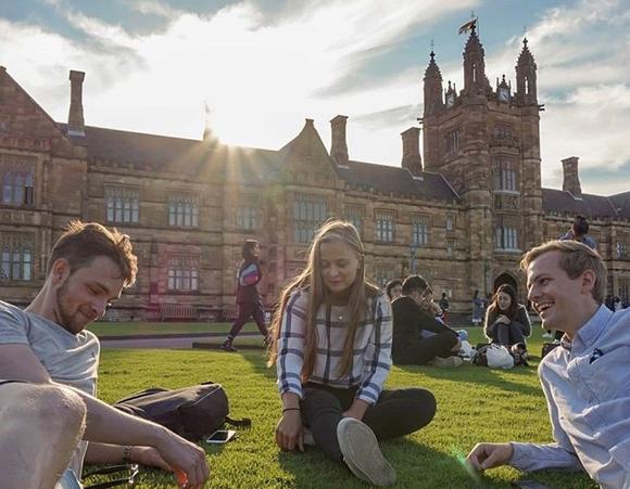 studenter på gresset utenfor campusbygget i Sydney