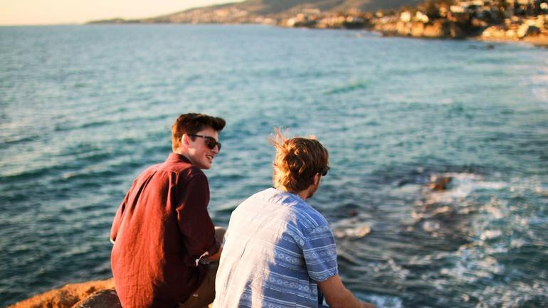 To gutter sitter ved havet og prater