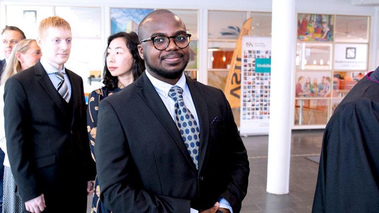 Christian Ahoba-Sam smiler i kamera rett før kreeringsseremonien