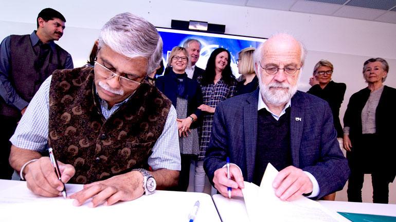 Selve signeringen med rektorene Nitin R. Karmalkar og Petter Aasen og delegasjonen stående bak som vitner