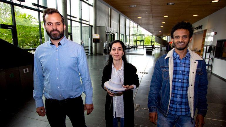 Studentene Henning, Dleen og Million gående på rekke med produktet i midten.
