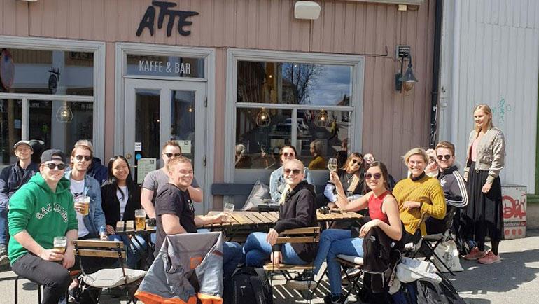 Gjester sittende utenfor hos Åtte i Kongsberg ser i kamera og skåler.