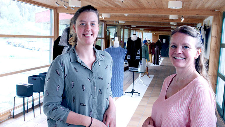 Nærbilde av smilende universitetslektor Martine Johannesen og førsteamanuensis Unni Boksasp med klær i bakgrunnen produsert av Rauland-studentene