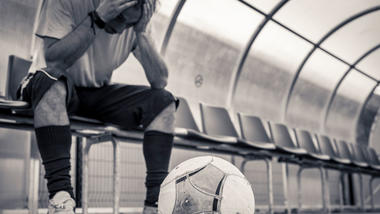 Stresset fotballspiller på benken. Foto