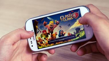 Nærbilde av en mobiltelefon med spill og hender som gamer.