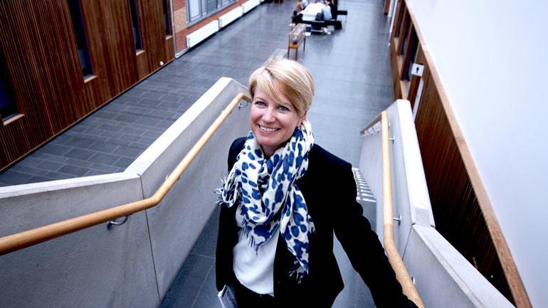 Astrid Camilla Wiig står i trappa på campus vestfold og smiler til kamera