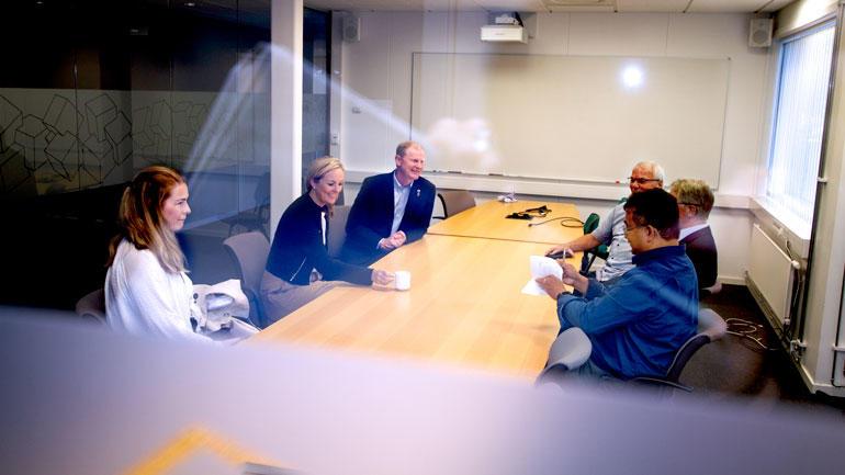 Stortingspolitikerne Erlend Larsen, Torill Eidsheim og politisk rådgiver Linn Pettersen sitter rundt møterommet og diskuterer sammen med USNs fagstab.
