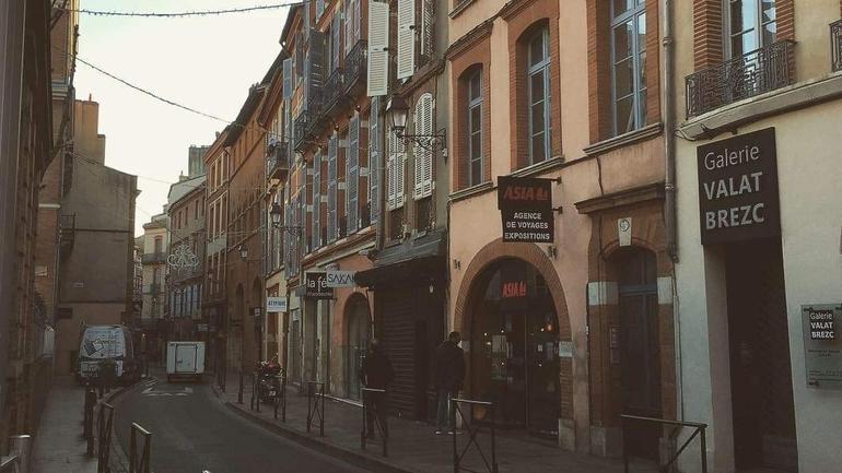Bilde fra en liten gate i Toulouse i soloppgang