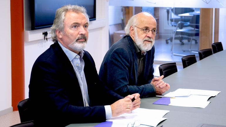 Nærbilde av  sittende Eldar Hauge og Petter Aasen med avtalen foran seg på bordet