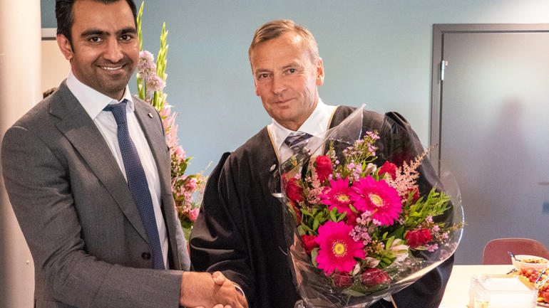 Ajmal Hafeez mottar blomster og gratulasjon fra dekan Hans Anton Stubberud ved USN Handelshøyskolen.