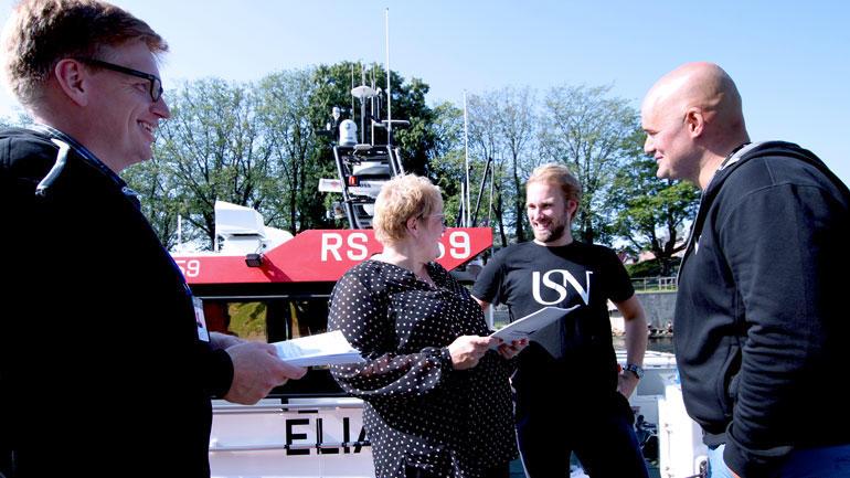 Studentene Kenneth Vidskjold, Christopher Sternefalk og Vegard Ravn leverer rapporten til en smilende  Venstre-leder Trine Skei Grande i Moss Havn