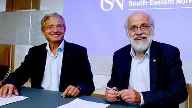 Gisle Dahn og Petter Aasen signerer avtalene og smiler til kamera