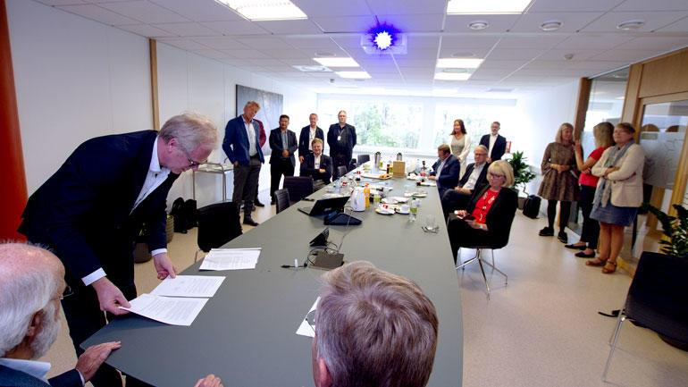 Oversiktsbilde over  begivenheten med signeringen med alle som er til stede og som står rundt langbordet i møterommet.