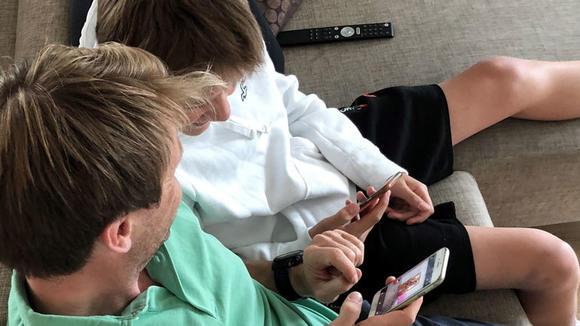Far og sønn ser på mobiltelefon sammen