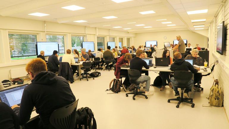 Det aktive læringsrommet er lagt opp med ni gruppebord og en skjerm der studentene følger undervisningen.